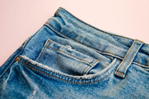 Джинсы на розовом столе. джинсовые элементы, карманы, швы крупным планом. порванные джинсы.