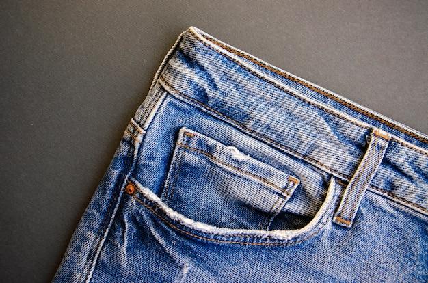 Джинсы на черном столе. джинсовые элементы, карманы, швы крупным планом. порванные джинсы.