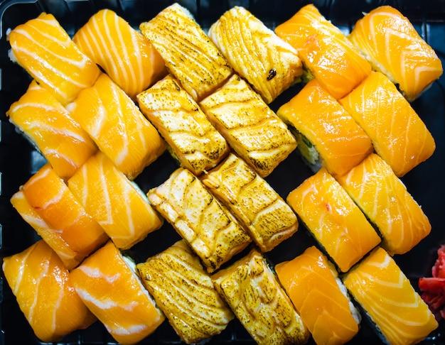 Свежие рулетики из лосося. рулетики из копченого лосося. набор роллов на доске, стол. один кусок рулона. доставка еды, суши. много рулонов. палочки для рулетов.