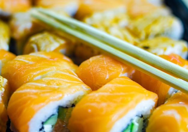 Свежие лосось филадельфия роллы. рулетики из копченого лосося. набор роллов на доске, стол. один кусок рулона. доставка еды, суши. много рулонов. палочки для рулетов.