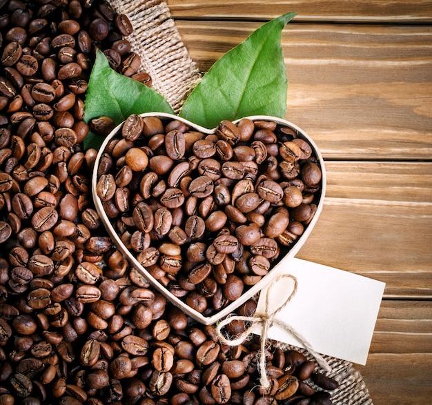 揚げコーヒー豆は木の板と黄麻布の上にハートの形であります。