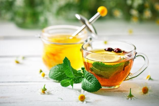 Здоровая чашка чая, банка меда и цветов.