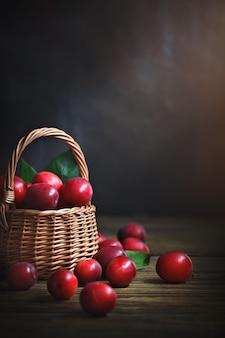Спелые красные сливы в плетеной корзине на деревянном столе.