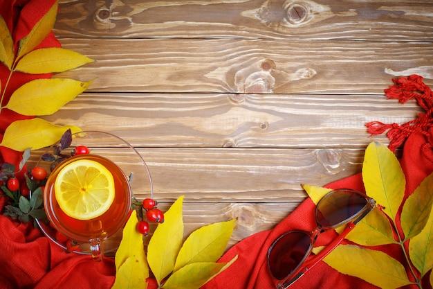 秋の紅葉、果実、新鮮なお茶で飾られたテーブル。秋。秋の背景。