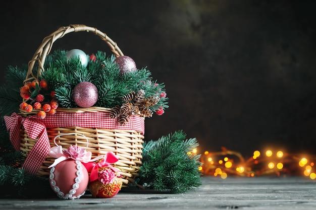 クリスマスのおもちゃと木製の背景にクリスマスプレゼント付きバスケット