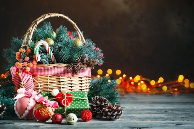 Корзина с елочными игрушками и новогодними подарками на деревянном фоне