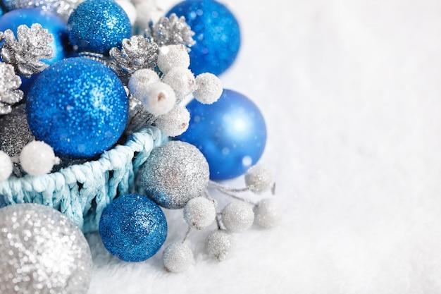 明るい背景に青と銀のクリスマスのおもちゃ。