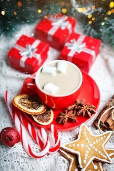 Чашка какао, печенье, подарки и еловые ветки на белом деревянном столе