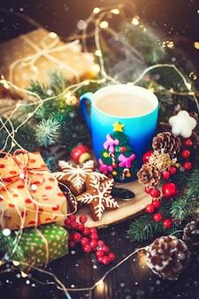 クリスマスの花輪の背景に熱いココアとクリスマスクッキーのカップ
