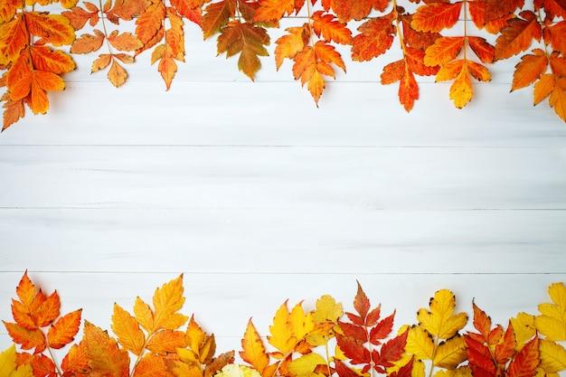 秋の葉で飾られた白い木製テーブル