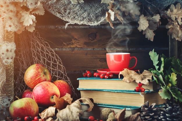 Осенний натюрморт с чашкой кофе, яблоками и осенними листьями.