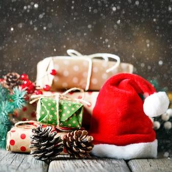 Деревянный стол украшен рождественскими подарками. площадь.
