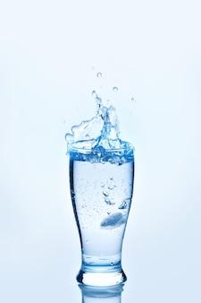 Кубики льда плескались в стакане воды. брызги воды,