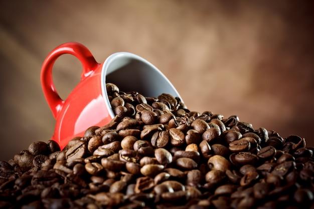 Красная керамическая кофейная чашка лежит в кофейных зернах