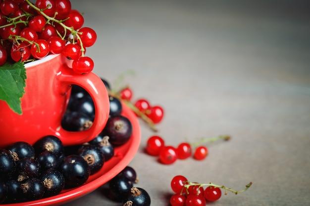 木製のテーブルに熟した赤と黒スグリ。