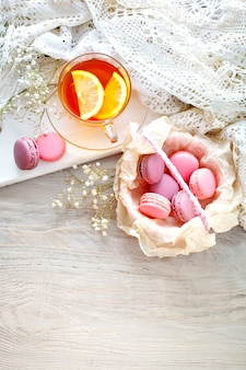 レモン、野生の花、白い木製のテーブルにマカロンとお茶
