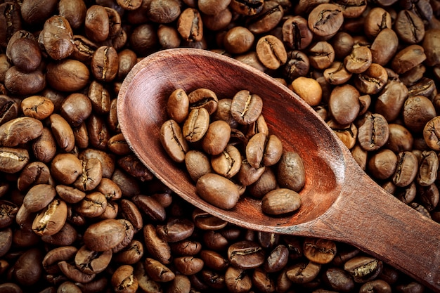 Кофейные зерна в коричневой ложке на вретище.