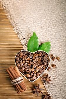 Жареные кофейные зерна лежат в форме сердца на деревянных досках и мешковины.