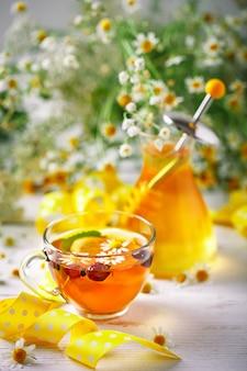 Здоровая чашка чая, банка меда и цветов. выборочный фокус.