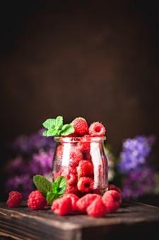 Малина в чашку на темном фоне. лето и концепция здорового питания. фон с копией пространства. выборочный фокус.