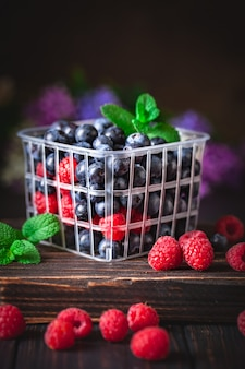 Малина и черника в корзине на темном фоне. лето и концепция здорового питания. фон с копией пространства. выборочный фокус.