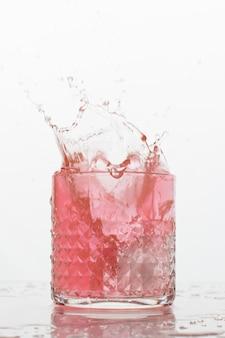 白い背景の上にはねかける新鮮な飲み物のガラス。冷凍モーション