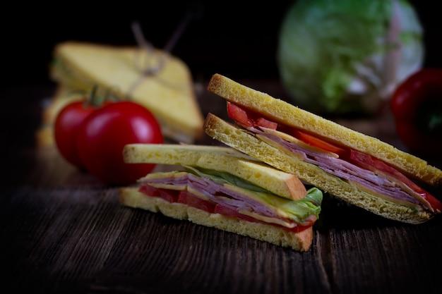 サンドイッチ、チーズ、ハム、濃い色の木製の背景に野菜とトーストのパンで作られました。
