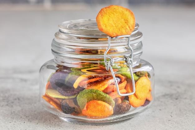 明るい灰色の背景にガラスの瓶にカラフルなミックス野菜チップ