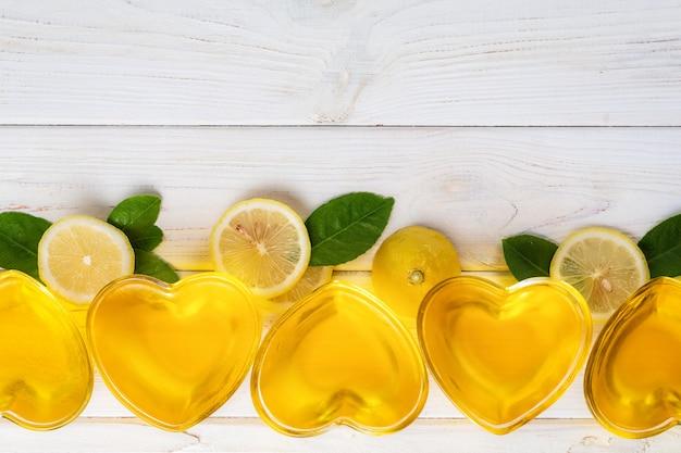 Желтое лимонное желе в форме сердца из стекла. желаем кусочки лимона и зеленые листья на белой древесине.