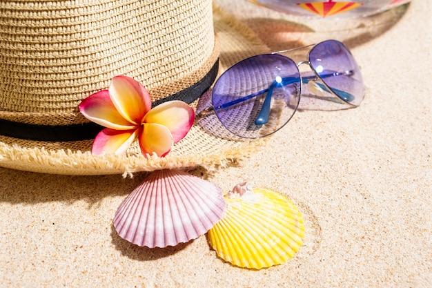 青いサングラス、カラフルな貝殻、ベージュの麦わら帽子、