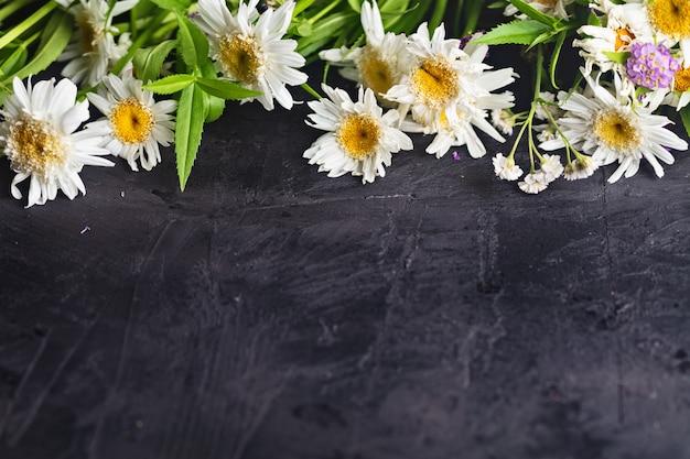 暗い木製のテーブルの上の白い庭のデイジーの花
