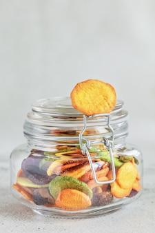 ガラスの瓶にカラフルなミックス野菜チップ、縦組版