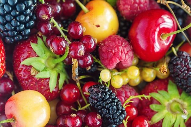 ミックスベリーイチゴ、ラズベリー、ブラックベリー、赤と黄色のスグリ、チェリーの背景。