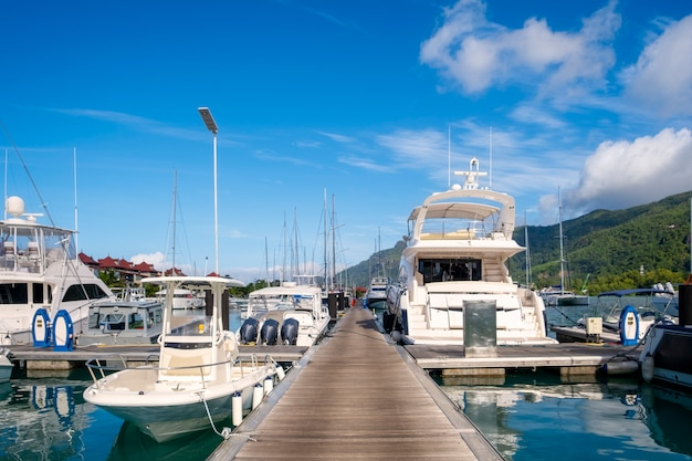 エデン島、マヘ島、セーシェルのマリーナで晴れた夏の日の豪華なヨットとボートと長い木製の桟橋