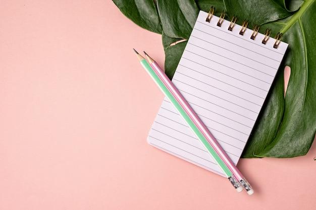 コピースペースとピンクのパステル調の背景にペンとモンステラリーフと空白のノートブックのトップビュー