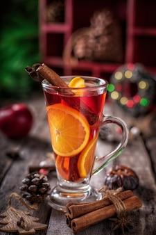 クリスマスのガラスは、スパイスと木製の素朴なテーブルにフルーツと赤ワインをグリューしました。