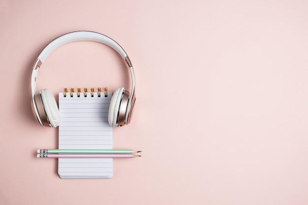 ピンクのヘッドフォン、空白のメモ帳、ピンクの背景、上面に鉛筆