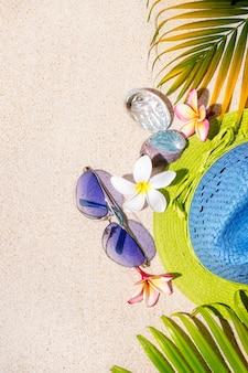 青と緑の麦わら帽子とサングラス、貝殻、フランジパニの花と緑のヤシの葉が砂の上にあります。