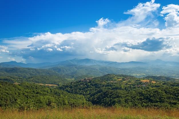 Ланге - холмистая местность в провинции кунео в пьемонте, северная италия. вид на долину после шторма. огромные белые облака на голубом небе.
