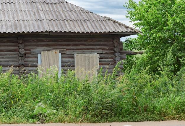 背の高い草が生い茂った古い木造住宅。放棄されたカントリーハウス。田園風景。