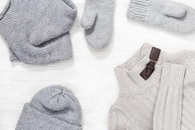 女性のニット帽、スカーフ、ミトン、暖かいセーター。女性のための秋と冬の服。上面図。
