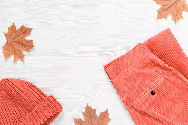 明るく暖かい服。女性のためのファッションの服。コーデュロイとコピースペースを持つ木製の背景の帽子からピンクのズボン。上面図。平干し。