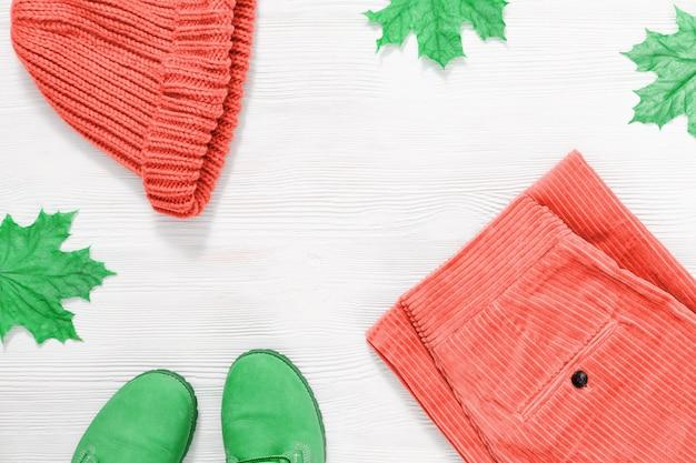 カエデの葉とコピースペースを持つ白いウッドの背景に女性のオレンジ色のニットキャップ、ズボン、革のブーツ。暖かい服トレンド色の秋とファッションのコンセプト。上面図。