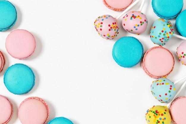 色とりどりのマカロンとケーキポップスをクローズアップ。コピースペースと背景の甘いデザート。各種クッキー。上面図。