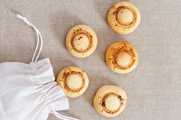 シャンピニオンの形のショートブレッドクッキー。テーブルの上の袋から焼き菓子がこぼれた。上面図。
