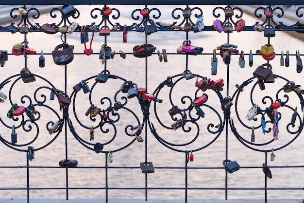 フェンスに掛かっている多くの異なるロック。橋の上の閉じたロック-結婚式の伝統。