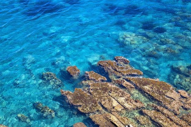 チェファル、シチリアのティレニア海岸。水に大きな石のある明るい青の深海。