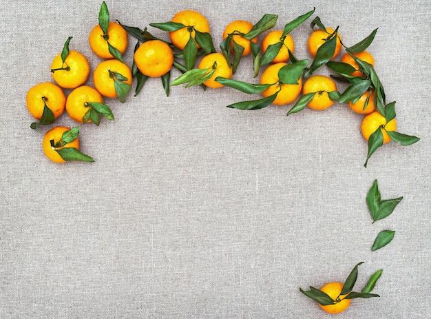 素朴な背景の葉とマンダリンオレンジ
