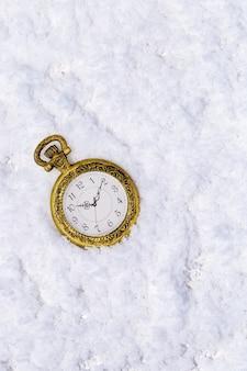 コピースペースと雪の背景にビンテージゴールデンポケット時計とメリークリスマスと幸せな新年のグリーティングカード。