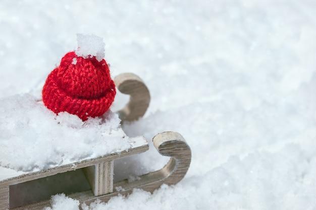 雪のクリスマスキャップと木製のそり